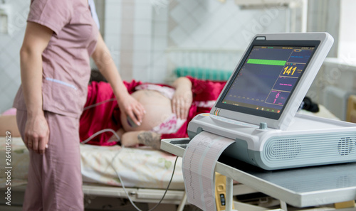 Obraz na plátně Pregnant woman with electrocardiograph check up for her baby
