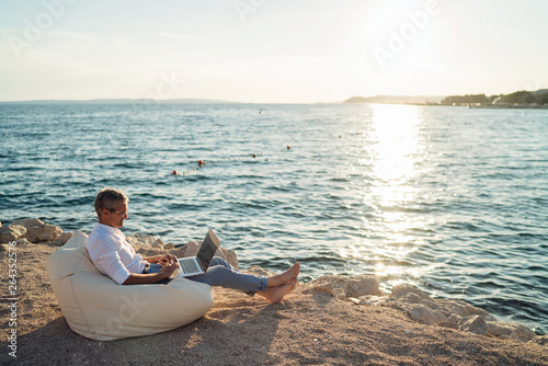 Foto Senior man working on his laptop lying on deck chair on the beach during sunset