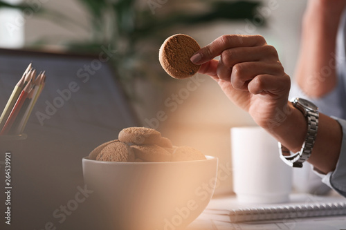 Photo Close up of businesswoman having sweet snack on a break at work.