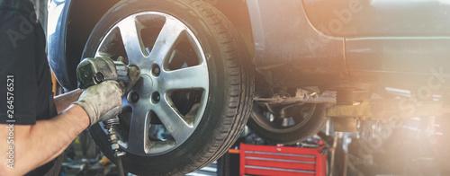Canvas Print car mechanic screwing the wheel at auto repair garage