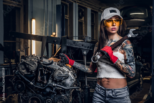 Sexual tattoed girl wearing cap and dirty clothes posing next to a car engine...