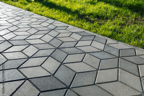 Photo The footpath in the park is paved with diamond shaped concrete tiles