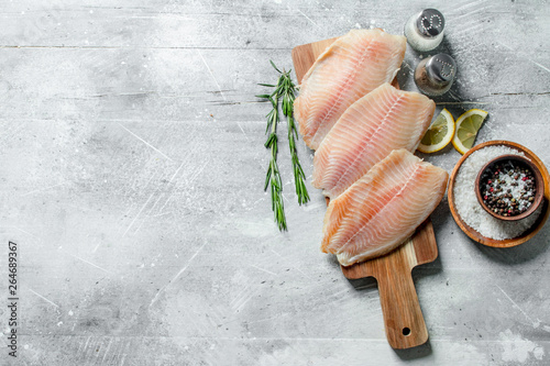 Photo Fish fillet on a wooden cutting Board with rosemary, spices and lemon slices