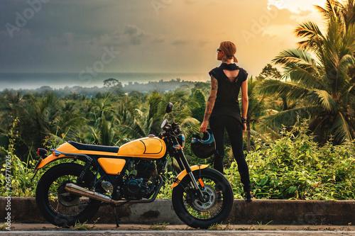 girl at sunset near the motorbike