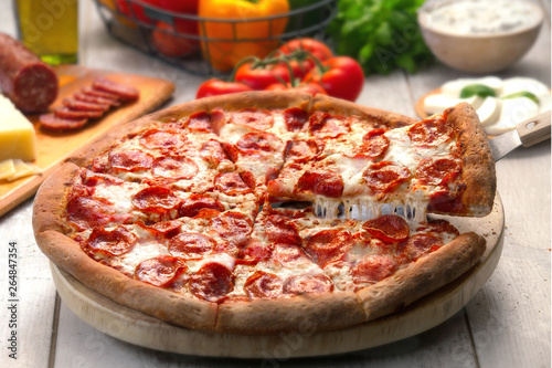 Delicious close up of a fresh handmade pepperoni pizza with cheesy slice next to organic ingredients
