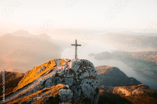Mountain summit cross on alpine peak at sunset Fototapet