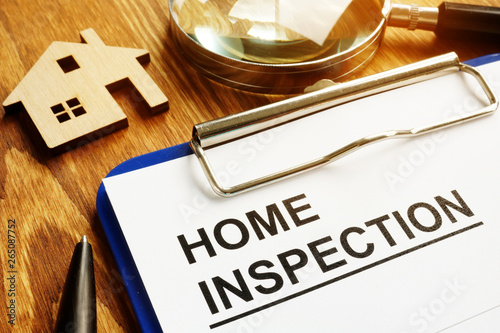 Photo Home inspection form with clipboard and pen.
