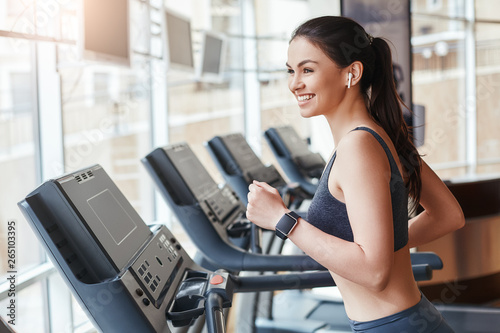 Get faster! Side view of young and cheerful woman in sportswear is running on a treadmill at gym and listening music Fototapeta