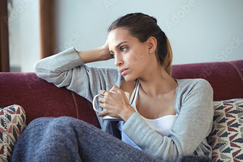 Fotografija Depressed young woman thinking about her problems while drinking coffee on sofa at home