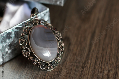 Leinwand Poster Oval pendant with grey natural stone on wooden background