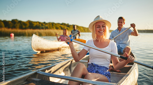 Tableau sur Toile Laughing young woman canoeing with friends on a sunny afternoon