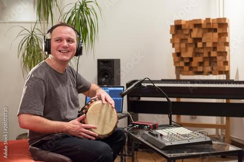 Fototapeta Musician playing djembe drum instrument in home music studio.