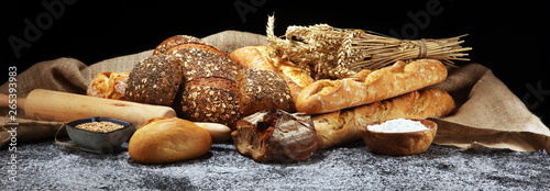 Photographie Assortment of baked bread and bread rolls on rustic grey bakery table background