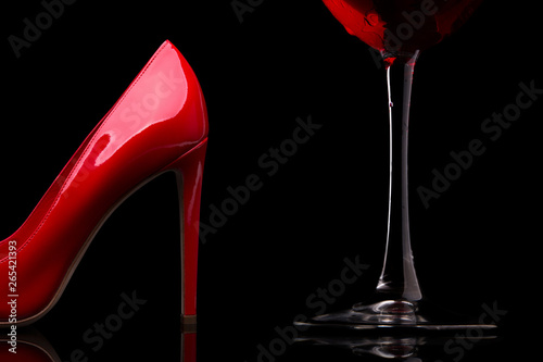 A glass of red wine and women's shoes with heels Fototapeta