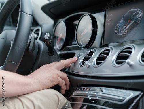 Man testing additional car control at luxury car фототапет
