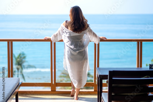 Stampa su Tela A beautiful asian woman standing and enjoy watching the sea view at balcony