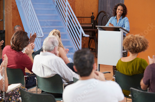 Photo Woman At Podium Chairing Neighborhood Meeting In Community Centre
