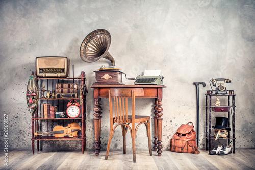 Fototapeta Antique chair, old typewriter, retro radio,  gramophone on wooden desk, books, clock, camera, binoculars, fiddle, keys on shelf, mask, cylinder hat, shoes, cane, backpack