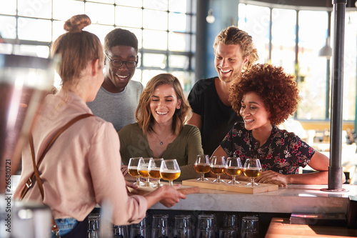 Fotografia Waitress Serving Group Of Friends Beer Tasting In Bar
