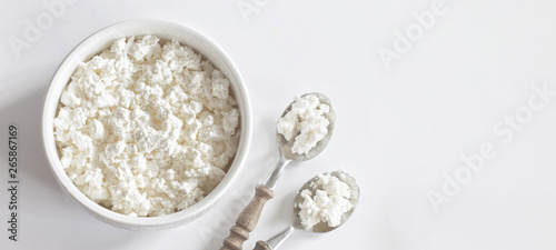Foto fresh cottage cheese in white porcelain Cup on white background top view