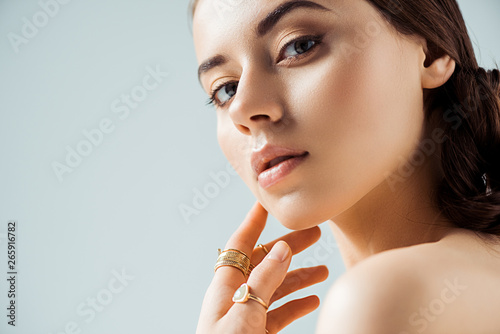Fototapeta young naked woman with shiny makeup and golden rings touching chin and looking a