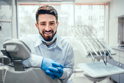 Canvas Print Front view of professional male dentist in white doctor coat and protective gloves sitting in dental chair and equipment, looking at camera and smiling