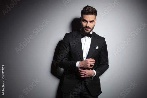 Obraz na plátně stylish businessman in black tuxedo adjusting his sleeve