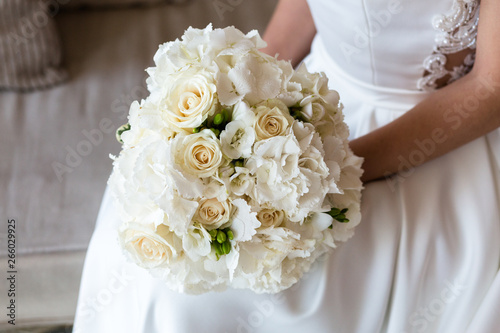 Fotografia Exquisite bridal bouquet of white roses, hydrangeas and freesia in the hands of