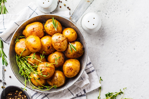 Stampa su Tela Baked potatoes in a cast iron skillet, top view.