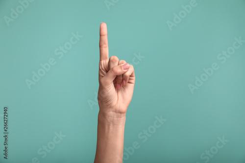 Canvastavla Gesturing female hand on color background