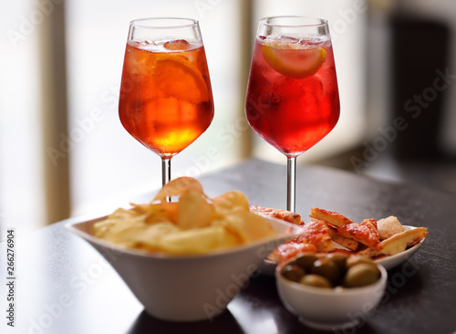 Foto Italian aperitives/aperitif: glass of cocktail (sparkling wine with Aperol) and appetizer platter on the table