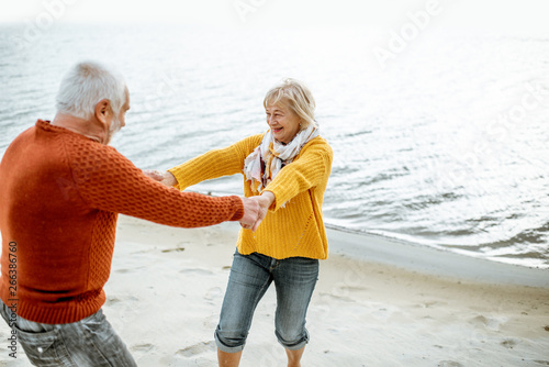 Lovely senior couple dressed in colorful sweaters dancing on the sandy beach, enjoying free time during retirement near the sea #266386760