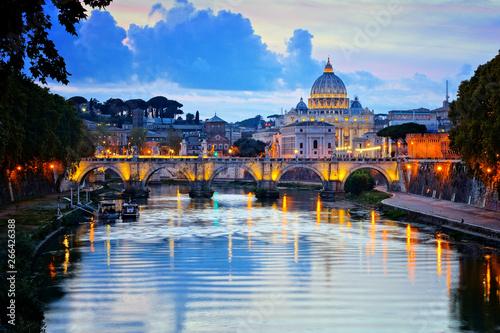Fényképezés View of Vatican City and St Peters Basilica across the River Tiber at dusk, Rome