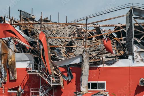 Billede på lærred Ruined and demolished industrial building after fire with broken roof, walls and