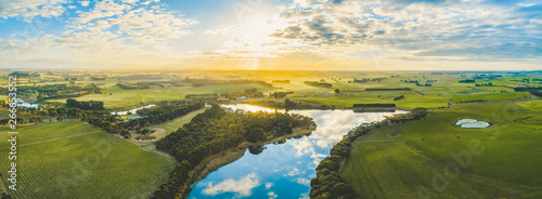 Fotografia Sun setting over scenic Australian countryside grasslands and pastures with rive