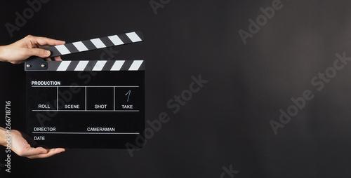 Canvastavla Hand is holding Black clapperboard or movie slate on black background