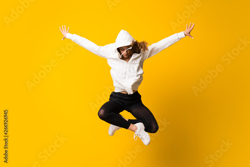 Valokuvatapetti Young woman jumping over isolated yellow wall