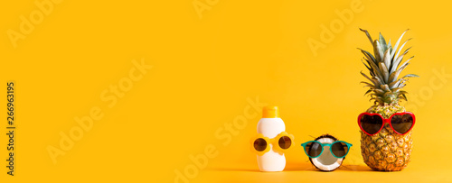 Fotografering Pineapple and coconut wearing sunglasses with sunblock on a solid background