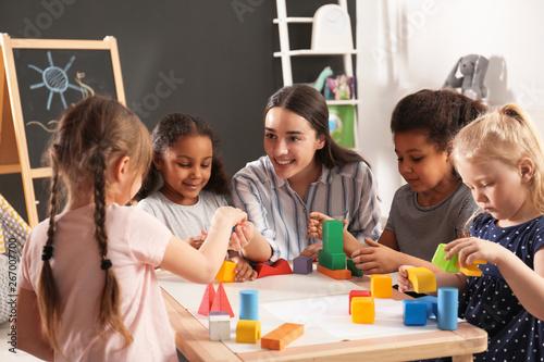 Wallpaper Mural Cute little children and nursery teacher playing with building blocks in kindergarten