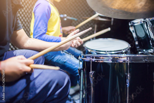 Fotografia hands of teacher with wooden drumsticks guiding boy in drum learning tutorial in