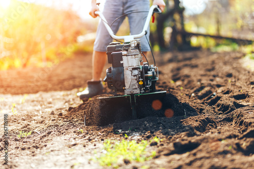 Leinwand Poster close up photo of young farmer gardener cultivate ground soil rototiller , tiller tractor, cutivator, miiling machine, prepare for planting crop, spring