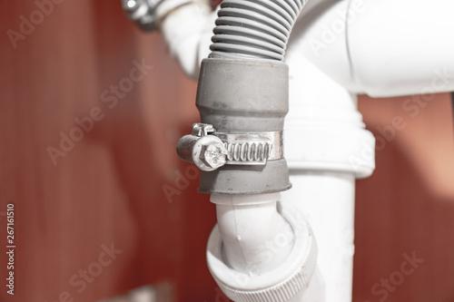 Metal clamp for connection of dishwasher drain hose under kitchen sink close up Fototapeta