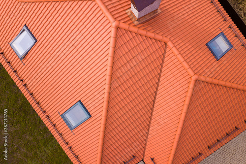 Obraz na płótnie Aerial top view of house metal shingle roof, brick chimneys and small plastic attic windows