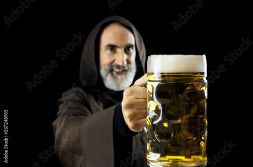 Photo An old friendly friar (Franciscan religious man), offering a giant mug full of fresh beer to the viewer