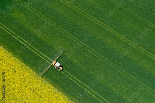 Aerial view of farming tractor plowing and spraying on field.  Agriculture. View from above. Photo captured with drone.