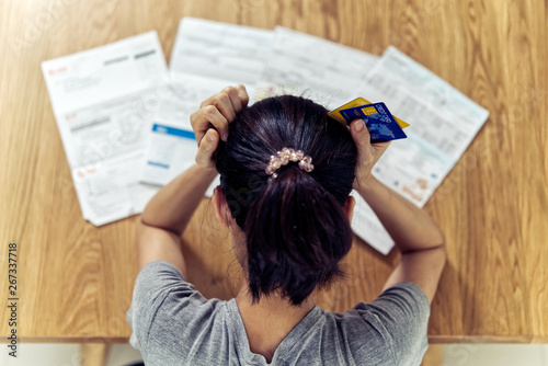 Top view of stressed young sitting Asian woman hands holding the head worry about find money to pay credit card debt and all loan bills Fototapet