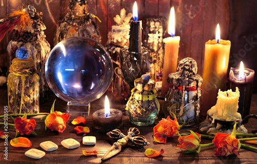 Photo Crystal ball with runes, black candle and witch magic bottle.
