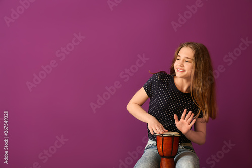 Stampa su Tela Teenage girl playing drum against color background