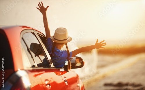 happy child girl goes to summer travel trip in car.