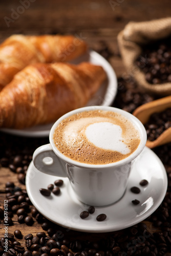 Photographie A cup of cappuccino with coffee bean as background.